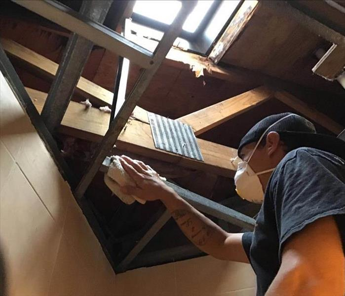 SERVPRO of Weston/West Davie wiping down the metal framing of a ceiling sky light leak.