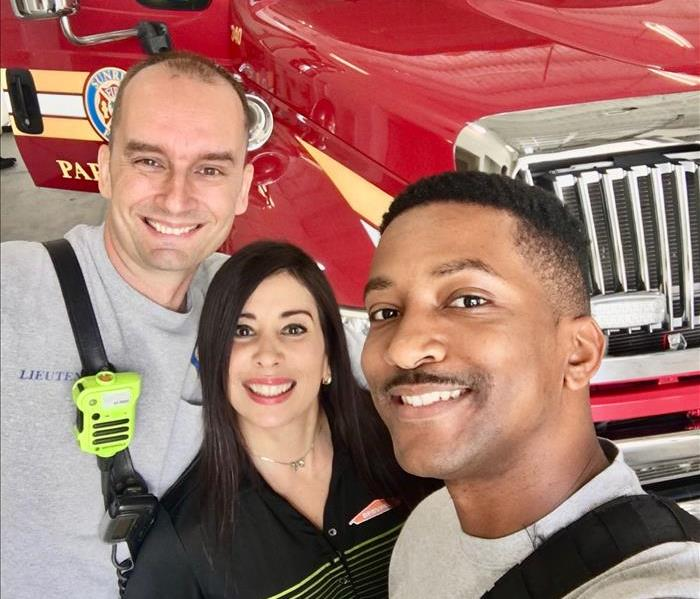 Three firefighters off duty posing with sales rep and a jar of candy