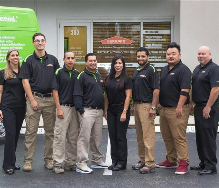 Team of people standing in between two green vans and infront of company building