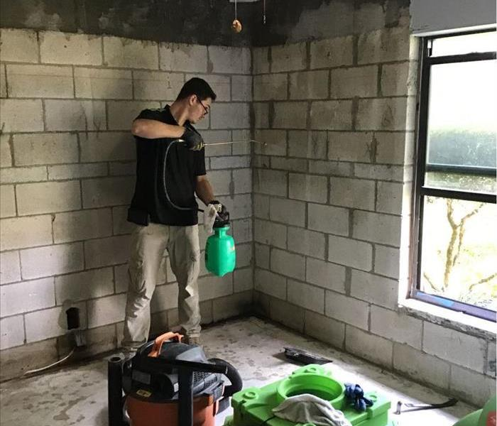 Man standing in the corner of the room spraying a chemical on a concrete wall