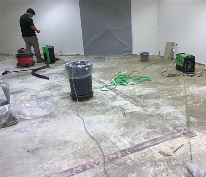 flooring removed exposing concrete floors and multiple pieces of drying equipment set up with a man checking their progress