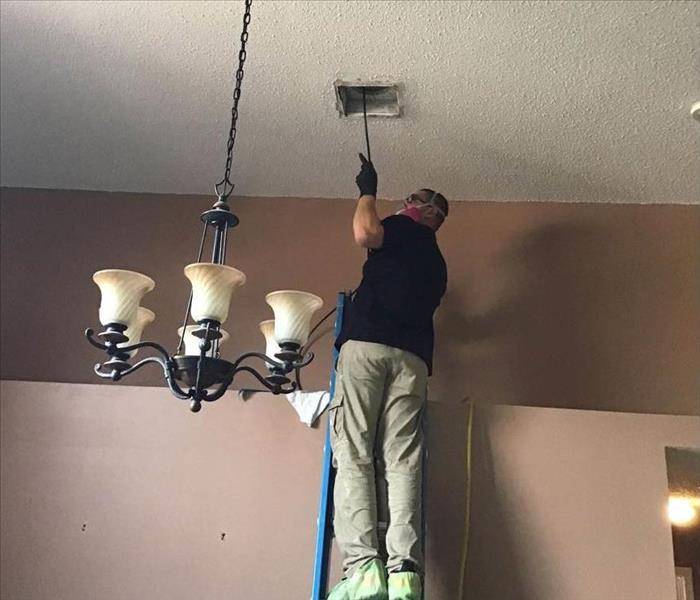 SERVPRO employee standing on a ladder to reach the duct work that needs a cleaning