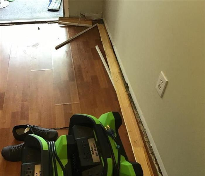 hallway with wood flooring and baseboards removed from wall, green fan set up to dry the wet area