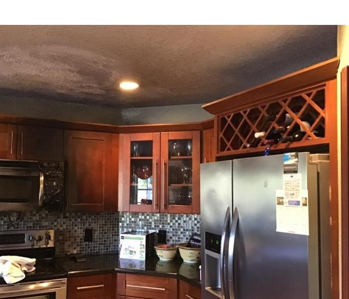 kitchen with medium brown cabinetry and stainless steel appliances has soot and smoke damage on ceiling and cabinents