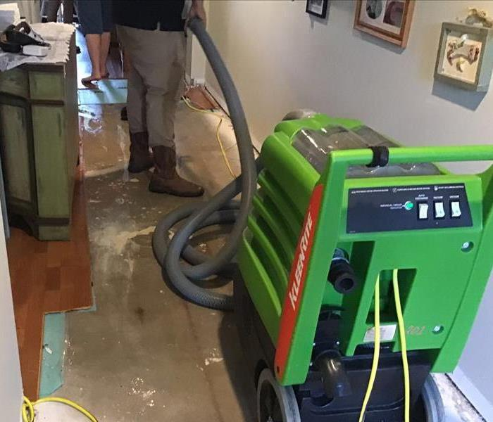 hallway with part of wood flooring removed exposing concrete and a man using a water extraction tool to suck up water on floo